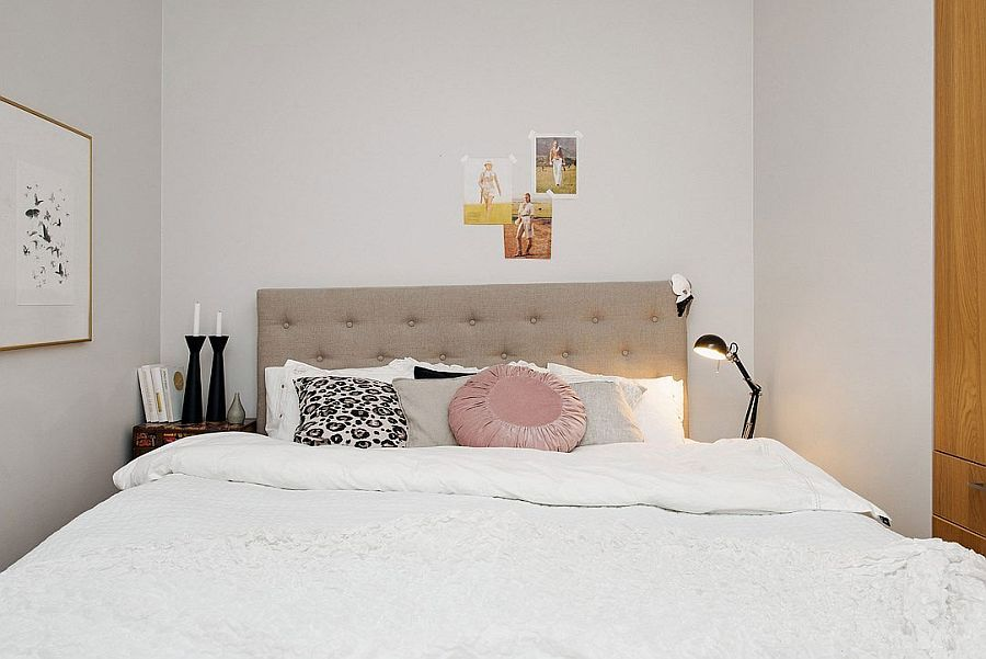 Tiny bedroom in white with small beside tables and floor lamp