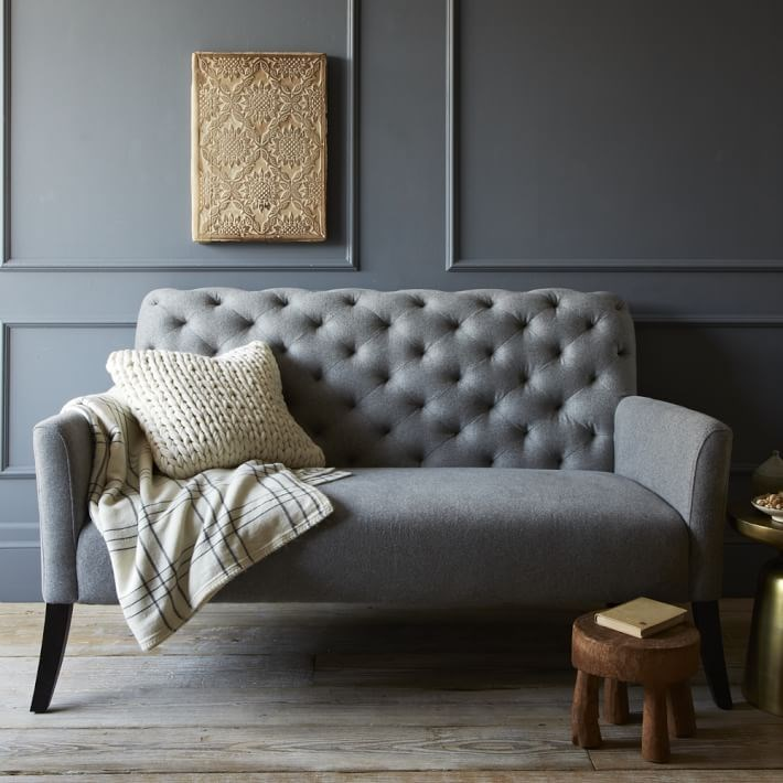 Tufted settee in a grey room with grey trim