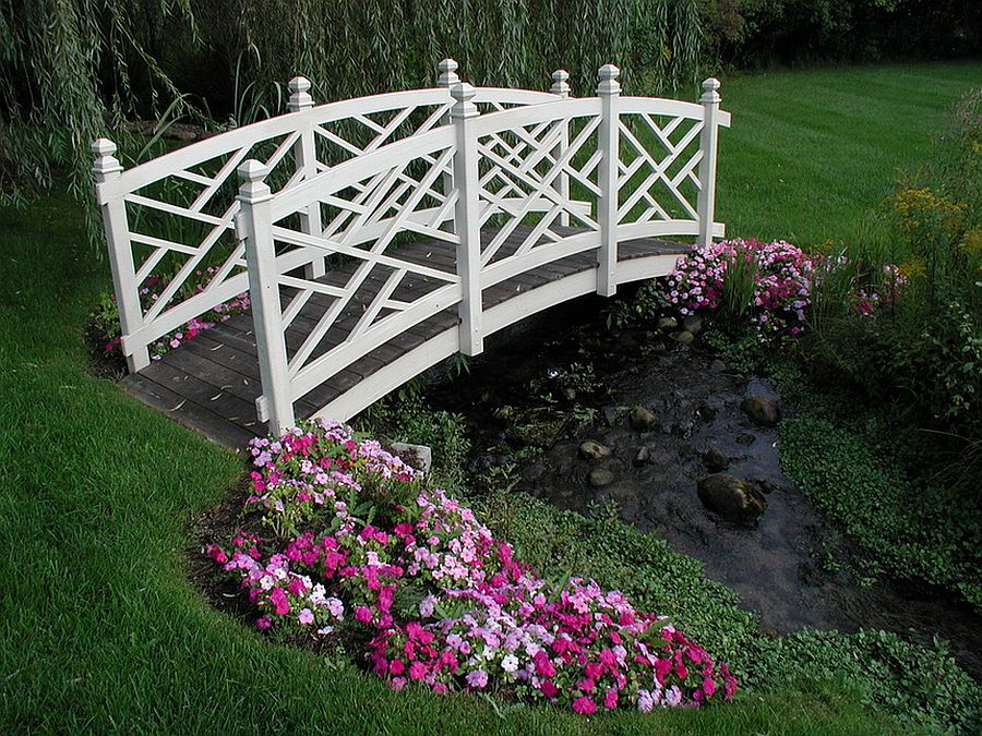 White garden bridge across natural backyard stream [Design: Specialty Gardens]