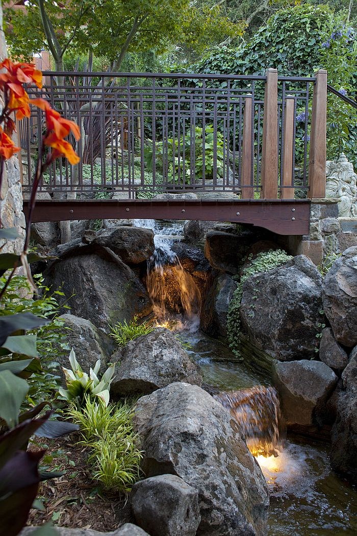 Wooden bridge over the waterfalls with beautiful lighting [Design: Pedersen Associates]