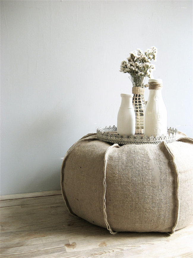 Burlap ottoman with a flat surface to display accessories