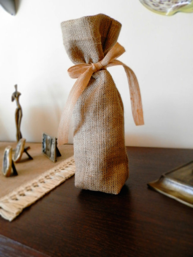 Burlap made into a simple wine bag and tied with ribbon