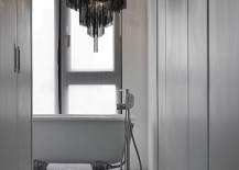 Chandelier above the bathtub adds dark contrast to the interior