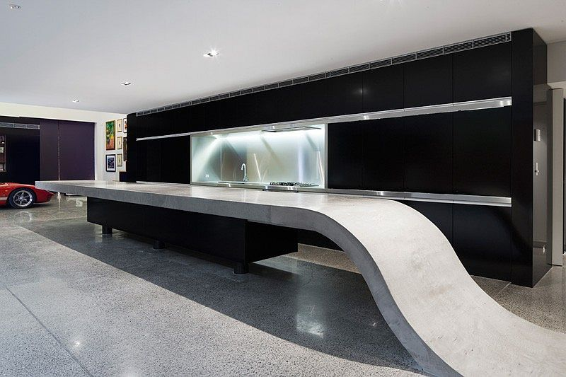 Custom concrete kitchen island with a black backdrop
