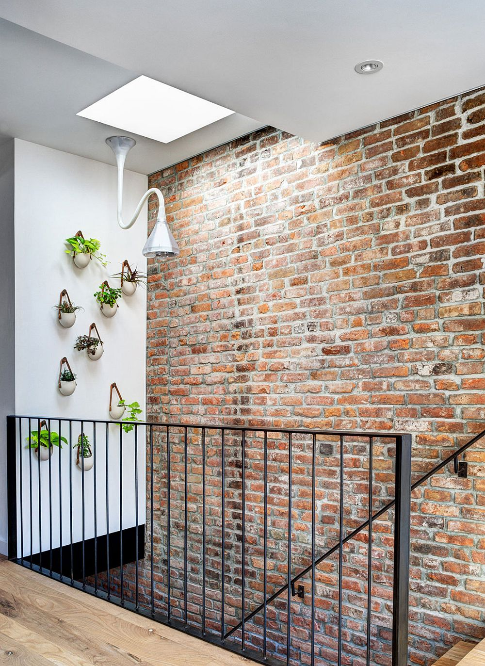 Gorgeous wall planters next to the staircase with skylight above
