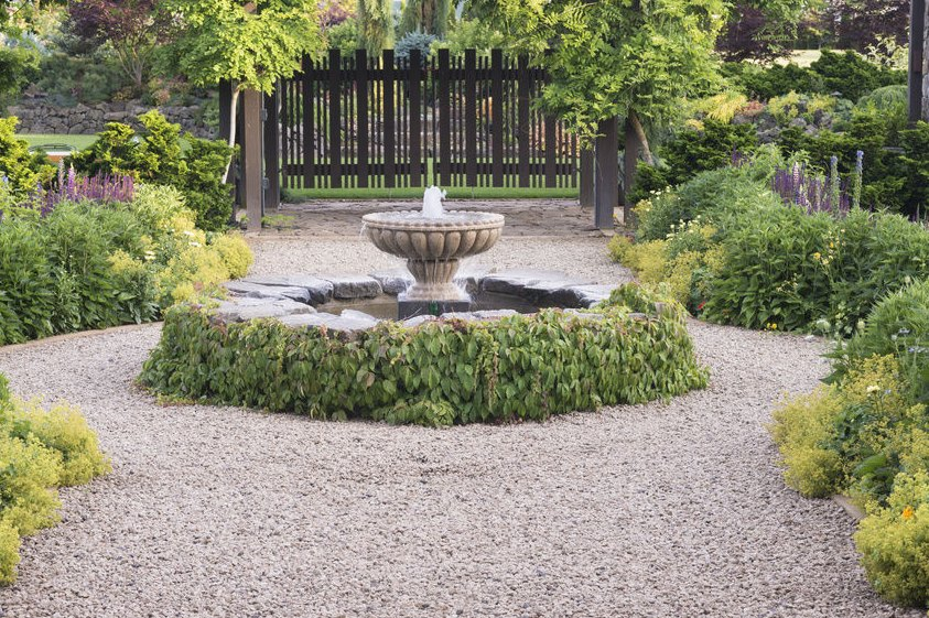 Graveled yard with a fountain focal point