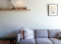 Gray couch in the lving room with a sleek floating shelf in the backdrop 217x155 North Fitzroy: Altering a Victorian Terrace House into a Breezy Modern Hub