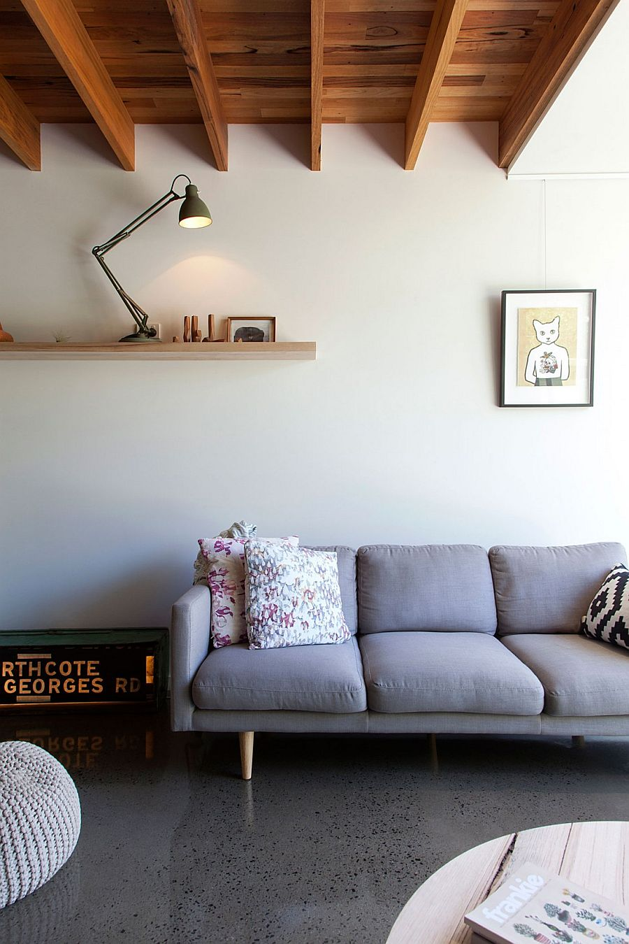 Gray couch in the lving room with a sleek floating shelf in the backdrop