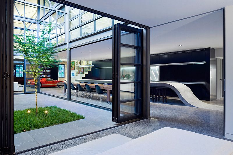 Large glass doors and windows create seamless interface between interior and courtyard