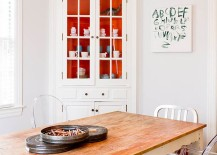 Pops or orange inside the corner cabinet add a touch of playfulness to the dining room