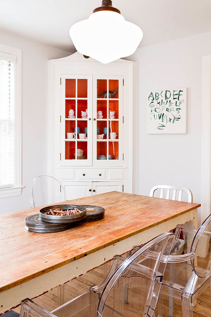 Pops or orange inside the corner cabinet add a touch of playfulness to the dining room [From: Rikki Snyder Photography]