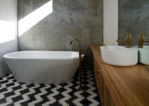 Rendered concrete walls of the bathroom stand in contrast to the geometric cement tiles