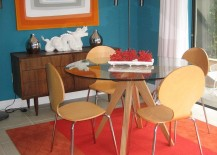 Rug and wall art bring orange into this midcentury dining room