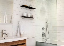 Sleek, dark floating shelves in the all-white contemporary bathroom hold their own