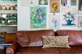 Vintage floral oil paintings shape a lovely gallery wall in this living room [From: Rikki Snyder Photography]