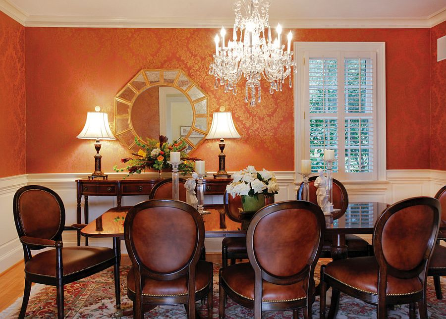 Wallpaper in orange and gold brings an air of luxury to the classy dining room