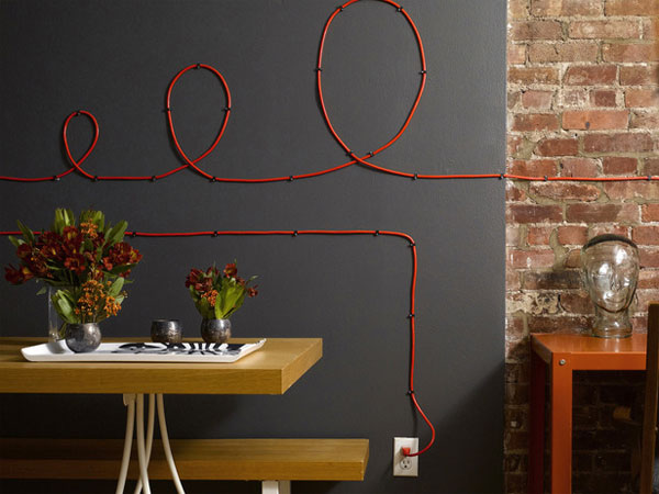 Red wire hung in loops on dark wall