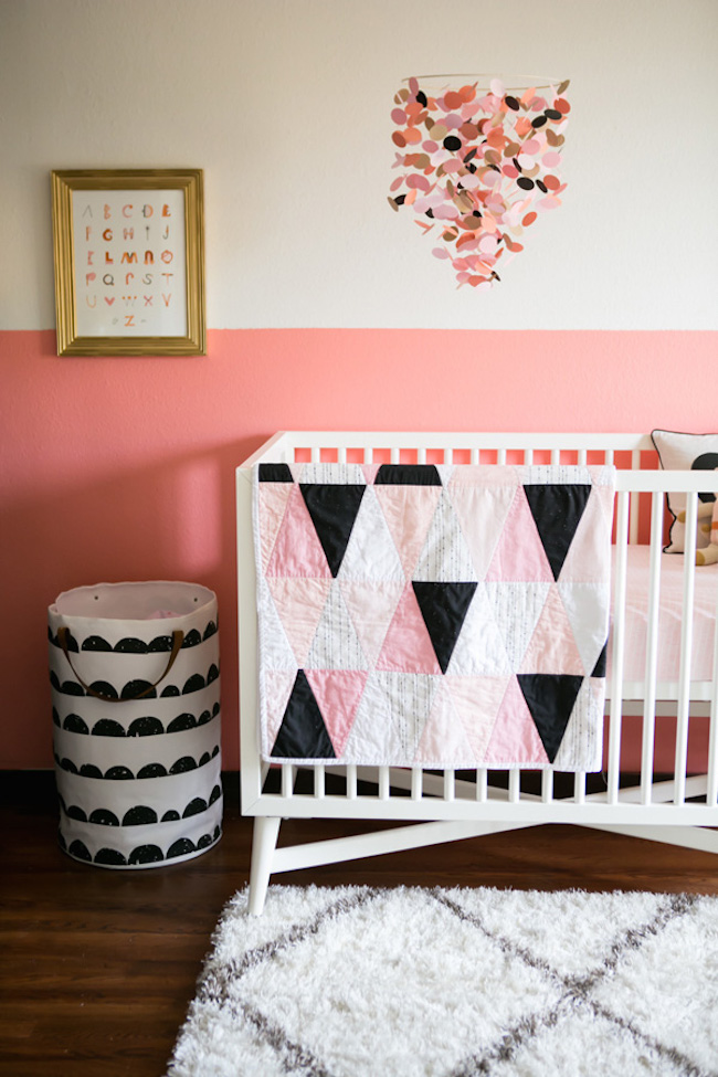 A half painted pink nursery paired with geometric crib bedding