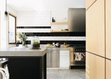 An innovative take on adding stripes to the kitchen backsplash with black and white tiles