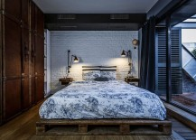 Bedroom with vintage suitcase-styled wardrobe and white brick wall