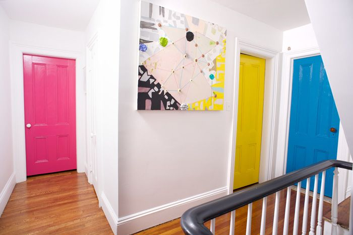 Brightly painted doors stand out against white walls