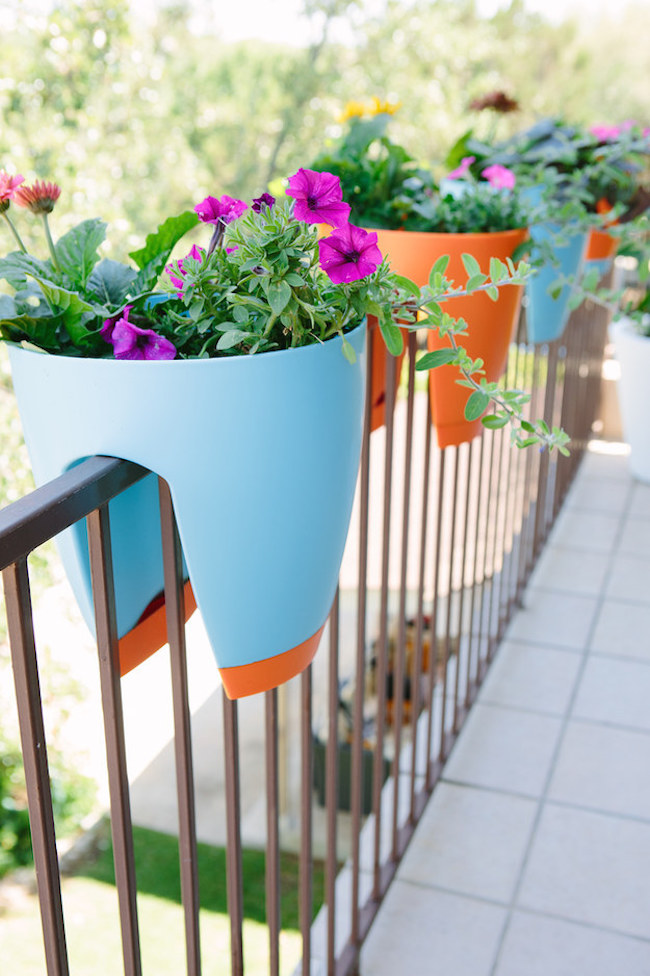 Colorful planters that sit on your balcony railing