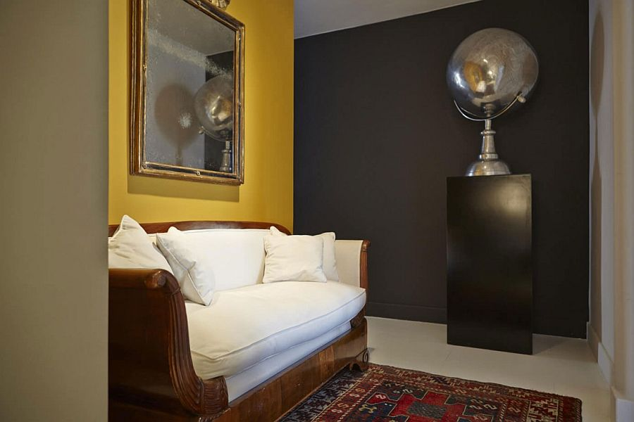 Couch with a wooden frame and accent wall in yellow