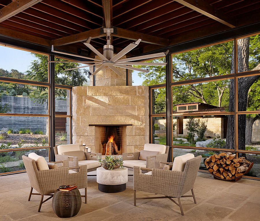 Cozy sunroom with a limestone fireplace [Design: Poet Interiors]
