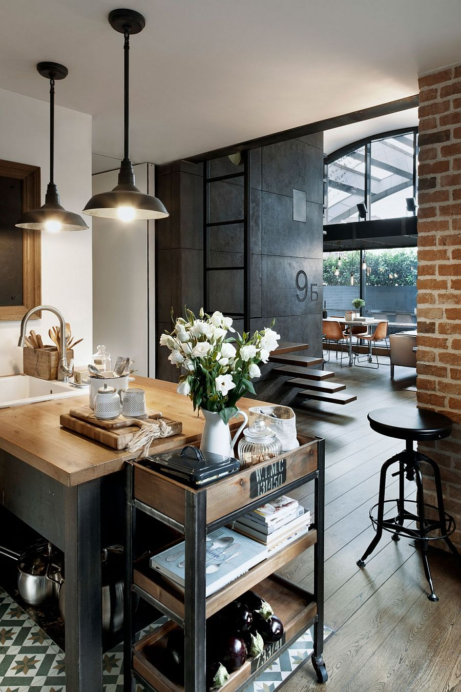 Custom crafted concrete panels, brick wall and lighting add industrial charm to the apartment