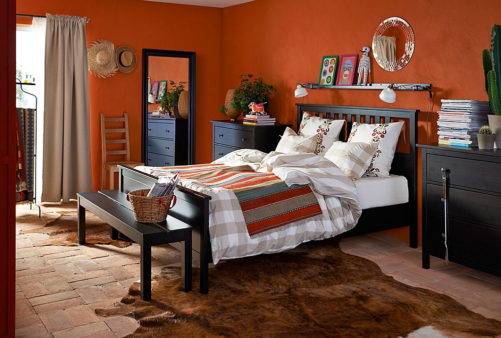Dark chest of drawers ground the vivacious bedroom in bold orange