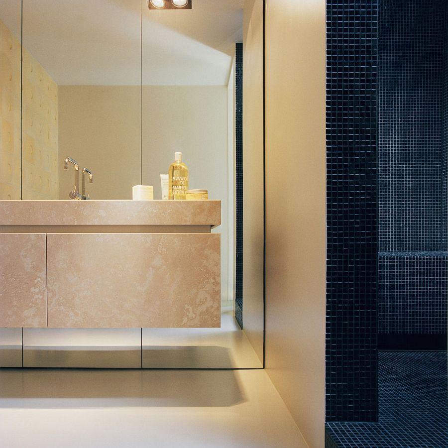 Dark tiles shape the shower area in the cozy bathroom