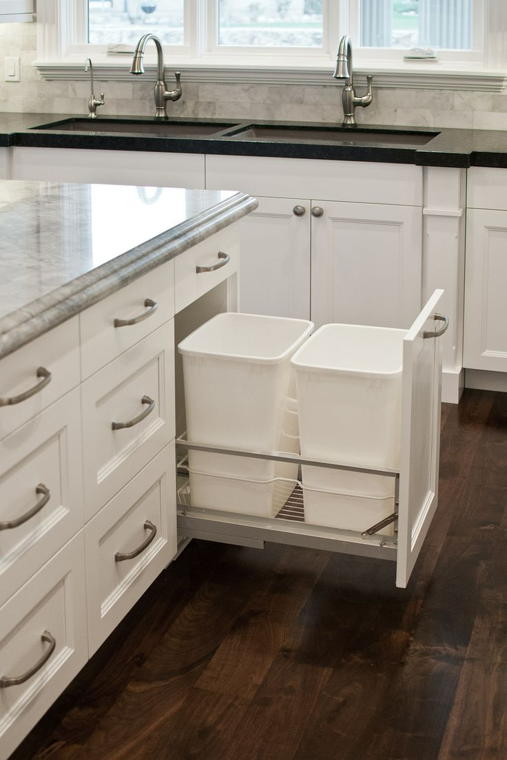 Double garbage cans hidden in white cabinetry