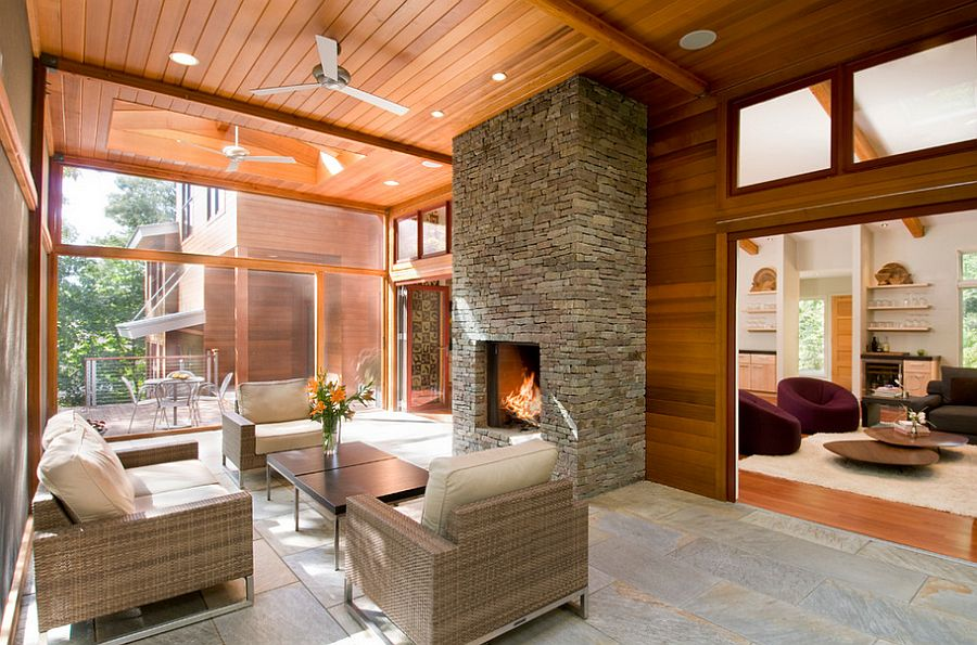 Elegant stone fireplace for the sunroom in wood and glass [Design: Hampden Design & Construction]