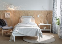 Elegant wooden bakdrop and TISDAG floor lamp create a refined ambiance in this small bedroom setup