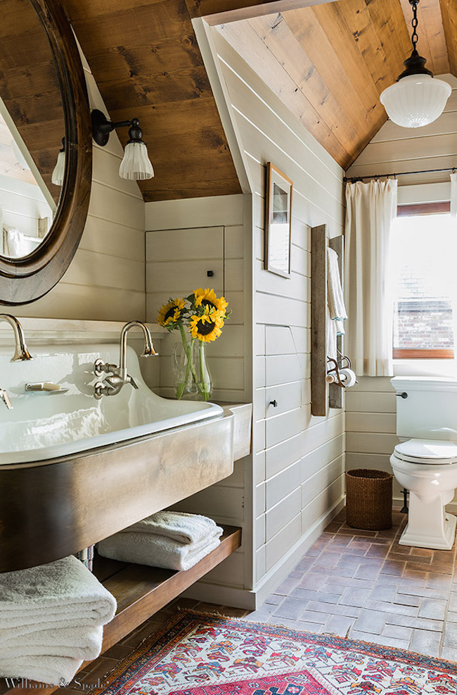 Gorgeous attic bathroom with wood ceiling and brick floor