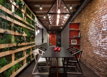 Green wall and brick wall border the intimate dining room with smart lighting