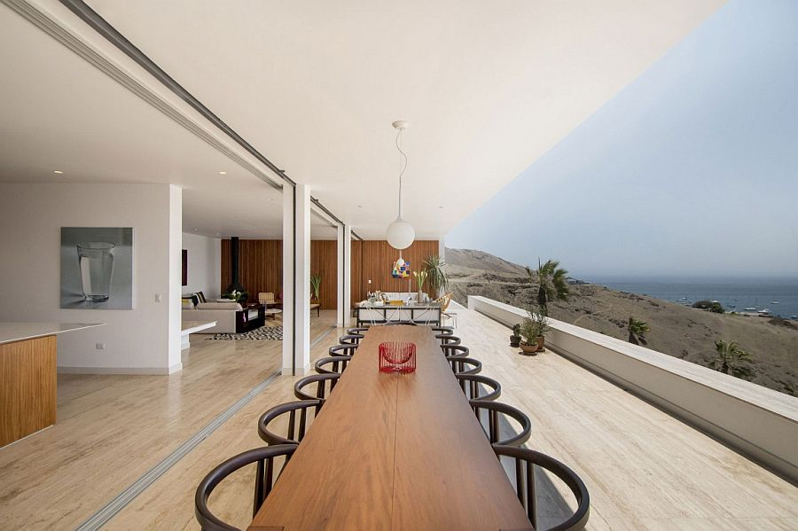 Large outdoor dining space and hangout connected with the living area visually and overlooking the Pacific