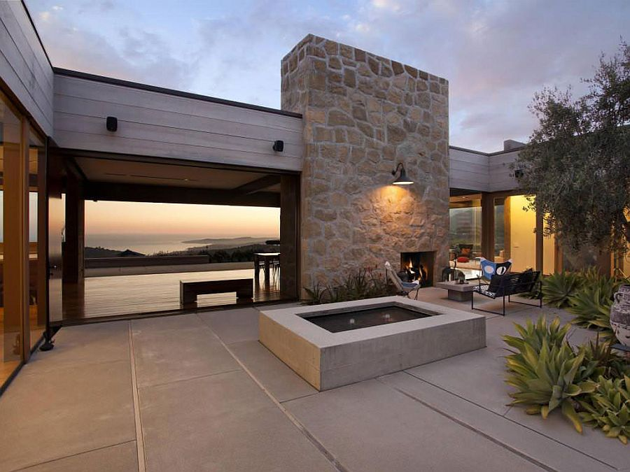 Large stone wall with fireplace shapes a cozy courtyard