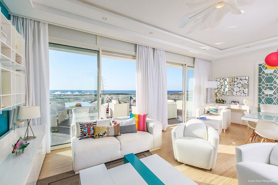 Living room in white with pops of brilliant color and ocean view