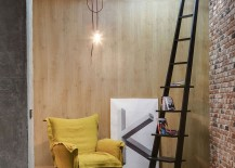 Lovely reading nook with brick wall, bright yellow chair and a stylish ladder used as book rack