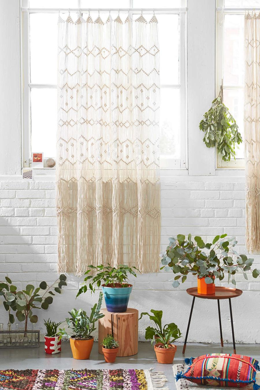 Macrame wall hanging against a white brick wall