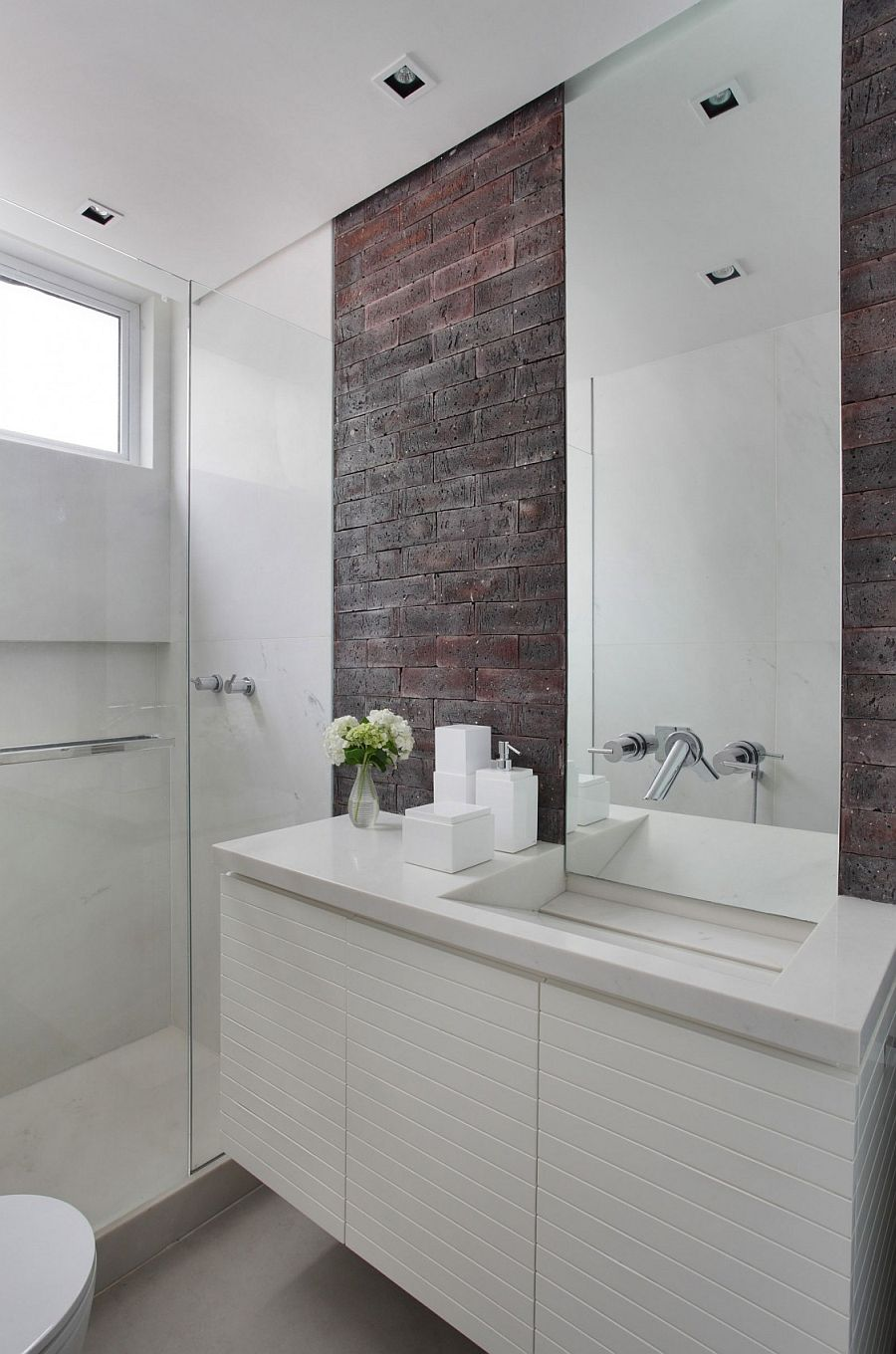 Modern bathroom in white with a brick wall