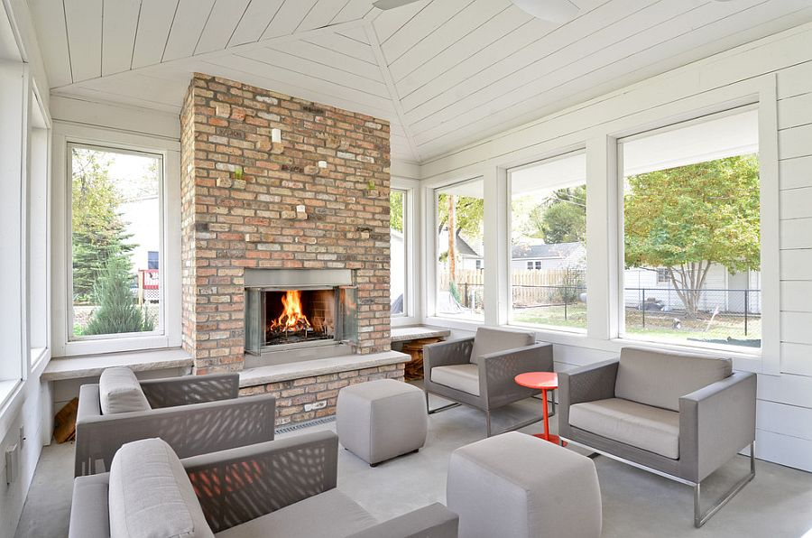 Neutral hues and brick fireplace shape sunroom with Scandinavian flair [Design: Refined LLC]