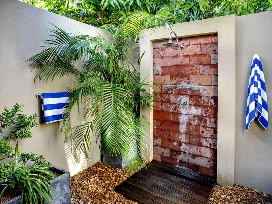 Outdoor shower with palm fronds and striped towels