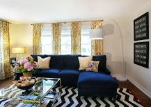 Plush-couch-in-navy-blue-and-coffee-table-in-glass-and-gold-for-the-trendy-living-room-217x155