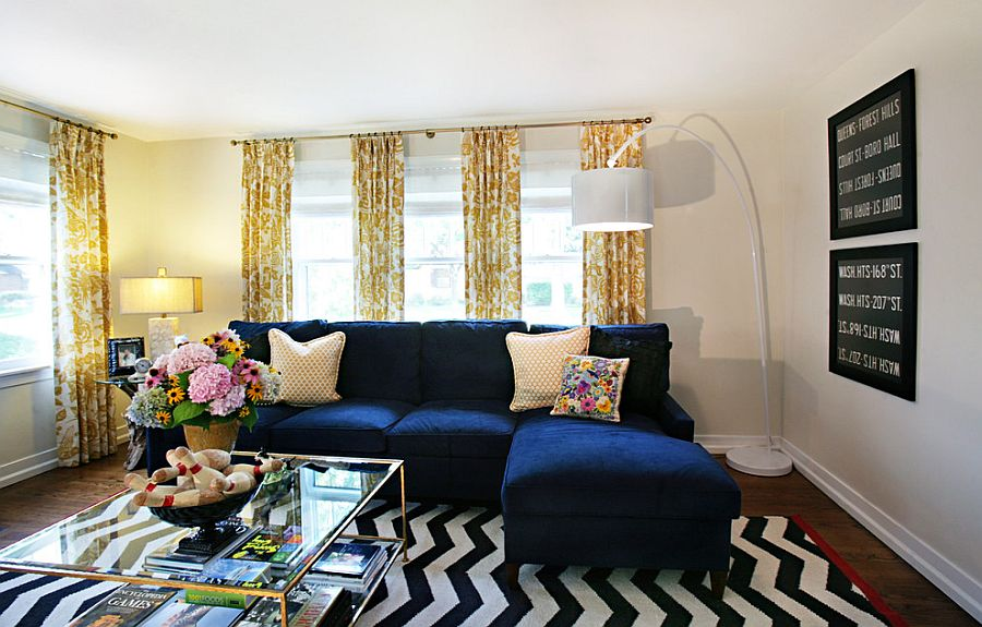 Plush couch in navy blue and coffee table in glass and gold for the trendy living room [Design: Debbie Basnett, Vintage Scout Interiors]