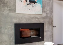 Precast concrete living room wall holds sleek modern fireplace and wall art