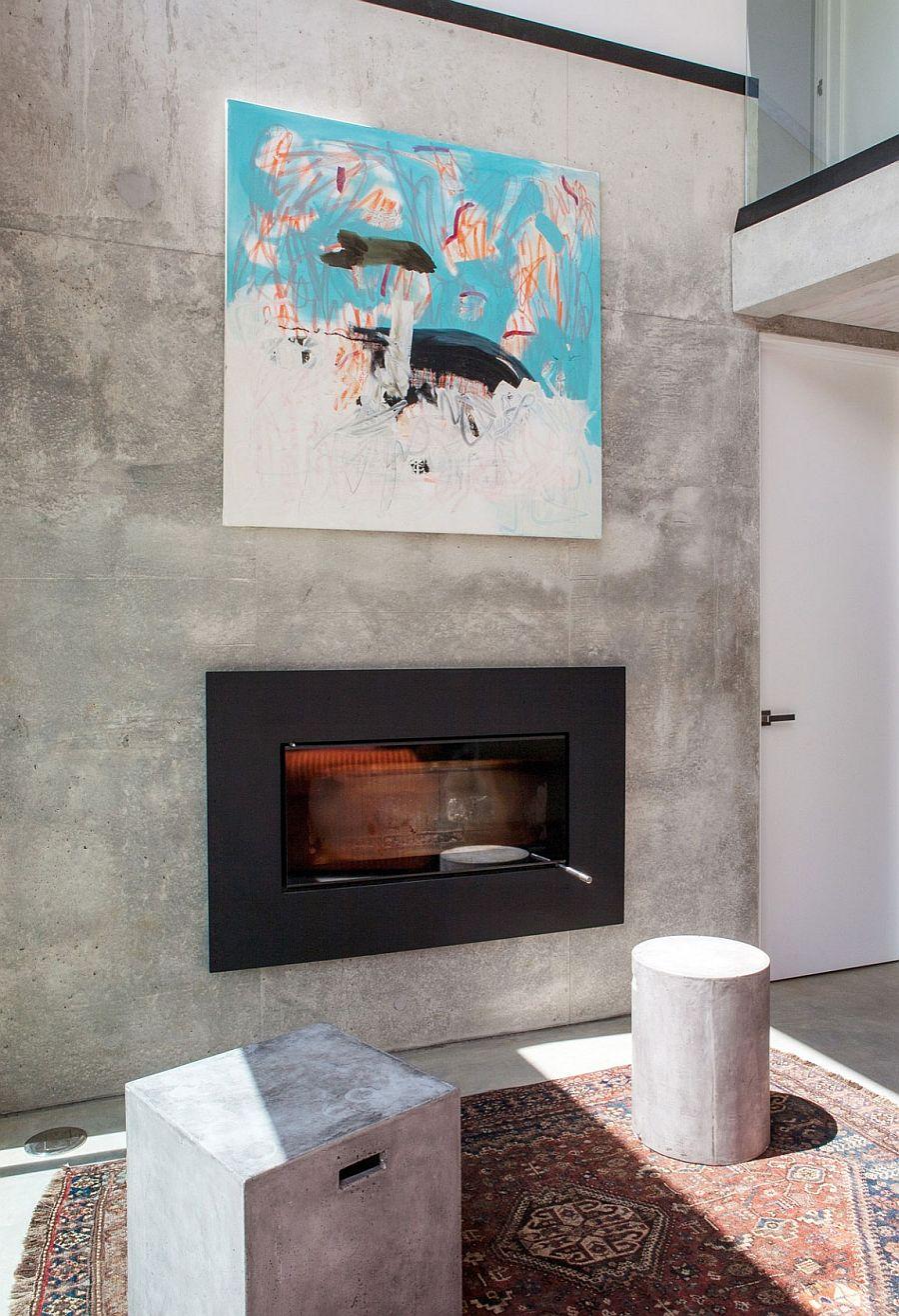 Precast concrete living room wall holds sleek modern fireplace and wall art