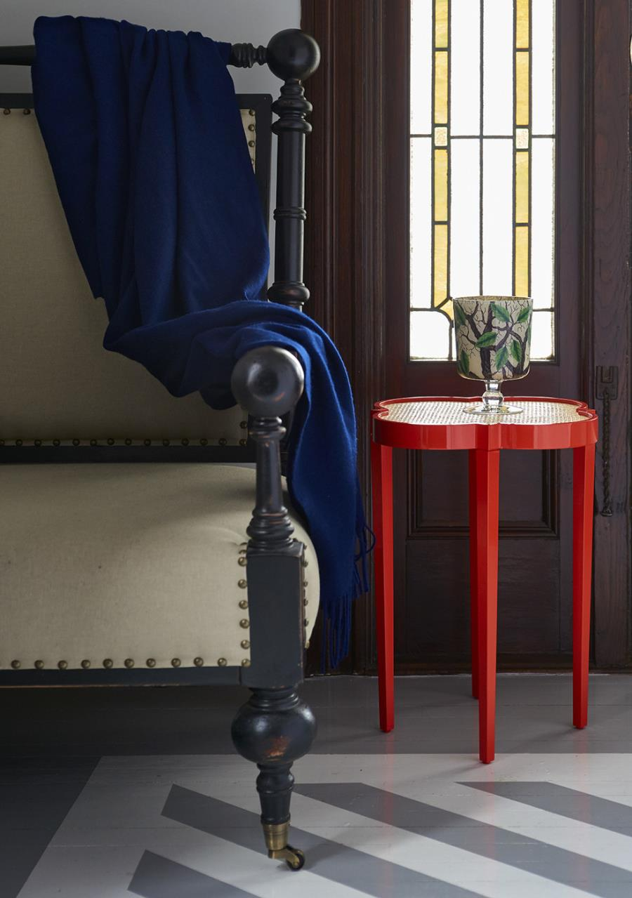 Red quatrefoil table in an entryway