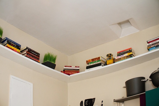 Shelves that surround the top of the kitchen ceiling